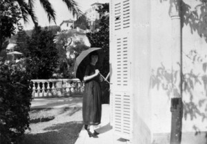 Katherine Mansfield, with a parasol, at the door on to the terrace at the Villa Isola Bella, Menton, France. Photograph taken by Ida Baker in 1920. Collections of the Alexander Turnbull Library.